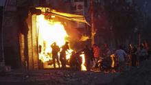 A shop is set on fire during violence between two groups in New Delhi, India (AP)