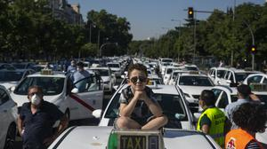 A child sits on the roof of a taxi during a taxi driver protest in Madrid (Manu Fernandez/AP)
