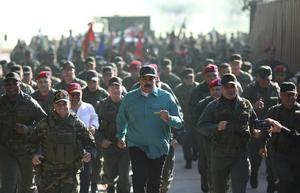 Venezuelan President Nicolas Maduro, centre, jogs alongside his defence minister Vladimir Padrino Lopez, right, and soldiers (Marcelo Garcia/AP)