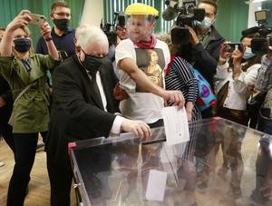 Jaroslaw Kaczynski, leader of Poland's right-wing ruling party, left, casts his ballot in the presidential election run-off in Warsaw (AP)
