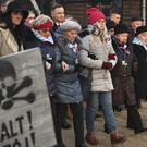 Poland's President Andrzej Duda walks along with survivors through the gates of the Auschwitz Nazi concentration camp in Oswiecim, Poland, Monday, Jan. 27, 2020. Survivors of the Auschwitz-Birkenau death camp gathered for commemorations marking the 75th anniversary of the Soviet army's liberation of the camp, using the testimony of survivors to warn about the signs of rising anti-Semitism and hatred in the world today.(AP Photo/Czarek Sokolowski)