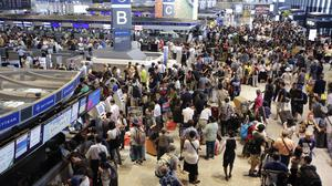 Passengers queue at the Delta Air Lines check-in counter at Japan's Narita international airport, where more than 1,000 people spent the night (AP)