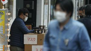 A man wearing a mask to help stop the spread of the new coronavirus in Tokyo (Eugene Hoshiko/AP)