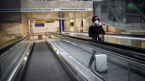 A woman wears a mask as she stands on an escalator inside MIlan's central railway station (Claudio Furlan/LaPresse/AP)