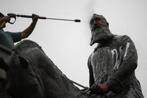 Workers clean graffiti from a statue of Belgium's King Leopold II in Brussels (AP)