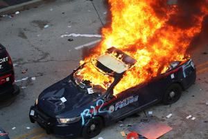 A police car burns after protesters marched to the Georgia State Capitol (Alyssa Pointer/AP)