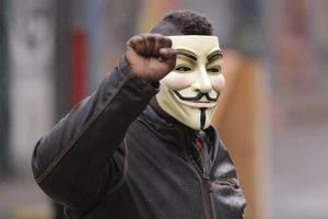 A protester raises his fist as he wears a Guy Fawkes mask near the Seattle Police Department East Precinct building (Ted S. Warren/AP)