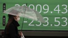 A woman walks past an electronic stock board showing Japan's Nikkei 225 index (Eugene Hoshiko/AP)