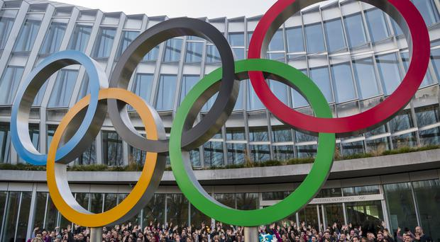 Young people pose behind the Olympic rings in Lausanne (Jean-Christophe Bott/Keystone via AP)