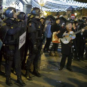 A Spanish man plays guitar as riot police search for protesters during a demonstration against the government in Madrid (AP)