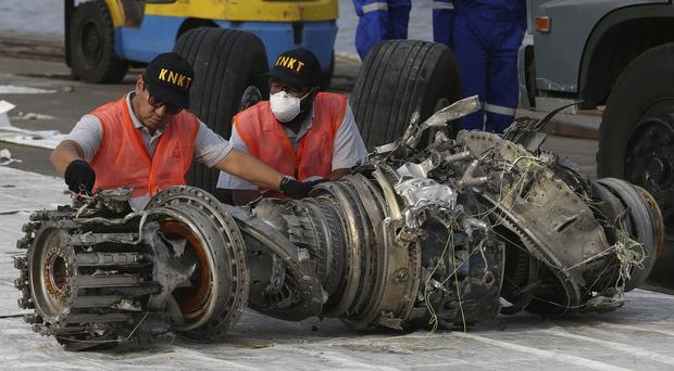 Officials inspecting the engine of the crashed Lion Air jet (Achmad Ibrahim/AP)