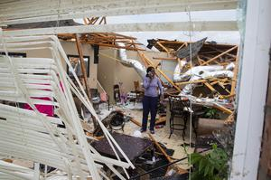 Rolanda Robinson calls family and friends from her brother's damaged home in Monroe (Nicolas Galindo/The News-Star via AP)