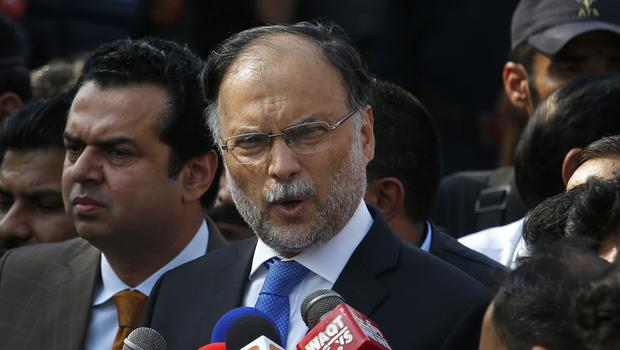 FILE – In this Oct. 2, 2017 file photo, Pakistani Interior Minister Ahsan Iqbal talks to journalists outside the accountability court, in Islamabad, Pakistan. Pakistani officials said a gunman opened fire on the interior minister after a public meeting, wounding him in the shoulder (Anjum Naveed/AP)