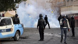 Police fire tear gas during clashes in the city of Ennour, near Kasserine (AP)