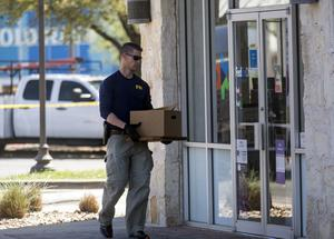 An FBI official carries items into a FedEX Office store as authorities investigate a recent string of package bombs. (Reshma Kirpalani/AP)