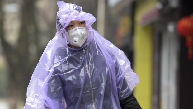 A masked woman wearing a raincoat carries food in Wuhan in central China's Hubei province (Chinatopix via AP)