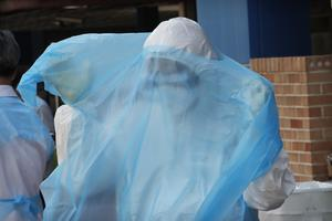 A medical worker wearing protective suits wears another a protective suit during Covid-19 testing at a hospital in Seoul (AP)