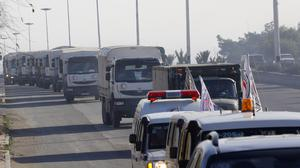 A convoy of trucks loaded with supplies heads out in Syria. In the besieged city of Deir el-Zour, supplies are running so short that people are selling their property for food or an exit permit (AP)