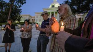 People hold a candlelight vigil for convicted murderer Tommy Arthur on the steps of the Alabama capitol building in Montgomery (The Montgomery Advertiser/AP)