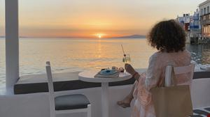 A visitor watches the sunset at a bar in an area known as Little Venice in the main town of the island of Mykonos, Greece (Derek Gatopoulos/AP)