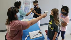 Science teachers check in students before a summer camp in Texas (LM Otero/AP)