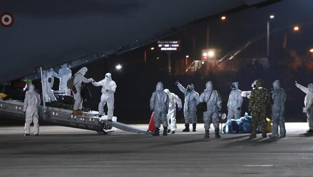 Turkish medical personnel work around an ambulance plane after it landed after flying from Wuhan, China (Huseyin Avci/Turkish Ministry of Health via AP)