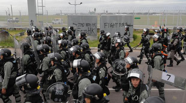 Police arrive after protesters blocked the road near the airport in Hong Kong (Kin Cheung/AP)