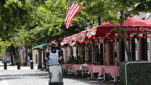 A worker walks past empty tables at the Hosteria Romana restaurant, which is closed to customers, during the coronavirus pandemic, Sunday, July 12, 2020, in Miami Beach, Florida (Lynne Sladky/AP)