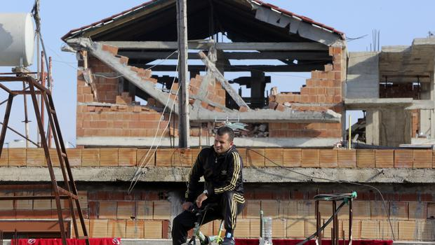 A man watches as rescuers search a damaged building in Durres, western Albania (Visar Kryeziu/AP)