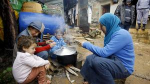 A Syrian refugee woman with her children prepares food near her tent. (AP)