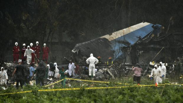 Rescue teams search through the wreckage site of a Boeing 737 that plummeted into a field (Ramon Espinosa/AP)