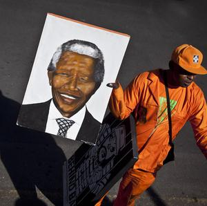 An arriving wellwisher carries a portrait of Nelson Mandela as he walks down the street outside the entrance to the hospital (AP)