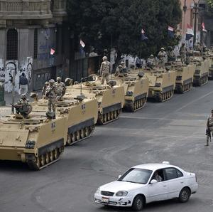 Egyptian army soldiers take their positions on top of their armoured vehicles to guard an entrance of Tahrir Square, in Cairo (AP/Hassan Ammar)