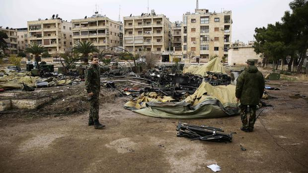 Russian soldiers check a burned medical tent after rebels launched a mortar shell at a field hospital in Aleppo (AP)