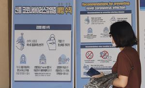 A visitor wearing a face mask walks near a banner showing precautions against coronavirus at the Gyeongbok Palace in Seoul (Lee Jin-man/AP)