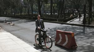 A man rides his bicycle along Reforma Avenue in Mexico City as authorities barred millions of vehicles from the streets (AP)