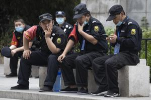 Security guards remove their masks for a smoke break in Beijing (Ng Han Guan/AP)