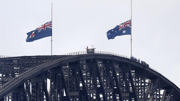 Flags on the Harbour Bridge fly at half-mast as a mark of mourning and respect in Sydney (Rick Rycroft/AP)