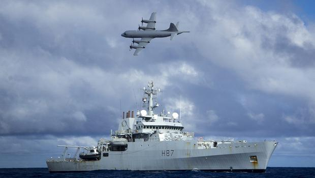 Survey ship HMS Echo, as a Lockheed P-3 Orion flies overhead, during the search for MH370 (Ministry of Defence/PA)