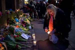 A woman lights a candle at a tribute to the victims at the synagogue in Copenhagen