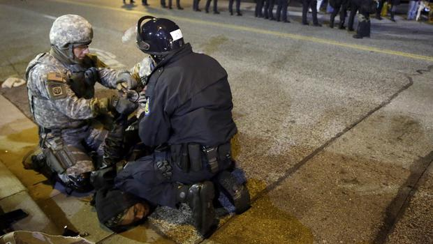 A protester is arrested in Ferguson during a demonstration outside the police department (AP)