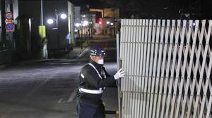 A guard opens the gate to the town in Futaba, Fukushima prefecture (Kyodo News/AP)