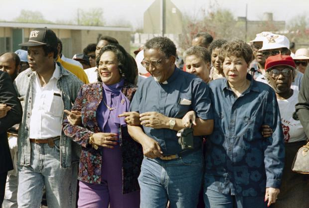 Coretta Scott King walks arm-in-arm with Southern Christian Leadership Conference President Joseph Lowery, 2nd from right, in Selma, Alabama, in March 1990 (Dave Martin/AP)