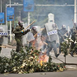 Riot police charge past a burning barricade as they engage in running battles with protesting students on a road next to Nairobi University (AP)
