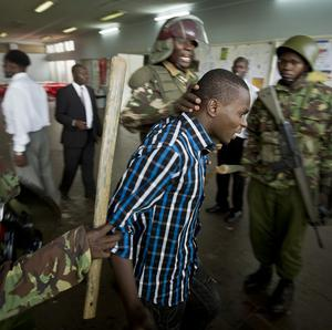 A Kenyan student is detained by riot police after surrendering in order to escape from a tear gas-filled building inside Nairobi University's main campus (AP)