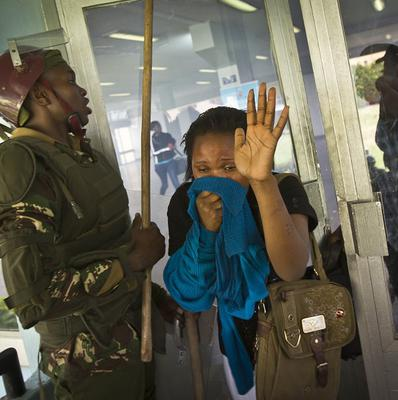 A student or member of university staff overcome by tear gas holds a cloth to her face (AP)