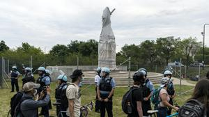 Activists protest around a statue of Christopher Columbus (Tyler LaRiviere/AP)