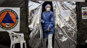 A paramedic wearing a mask gets out of a tent set up outside the emergency ward of the Piacenza hospital in northern Italy (Claudio Furlan/Lapresse via AP)