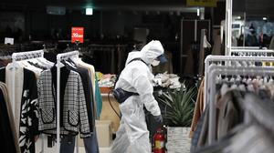 A worker wearing protective gear sprays disinfectant as a precaution against the new coronavirus at a department store in Seoul (Lee Jin-man/AP)