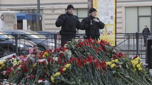 Police officers stand in guard at a symbolic memorial at Technologicheskiy Institute subway station in St. Petersburg, Russia.